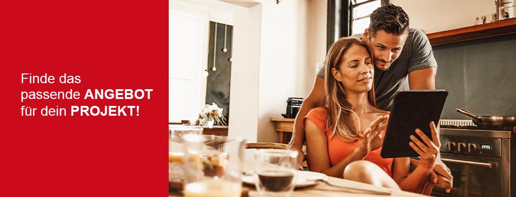 Mann und Frau sitzen am Frühstückstisch und lesen die Onlinebeilage auf dem Tablet